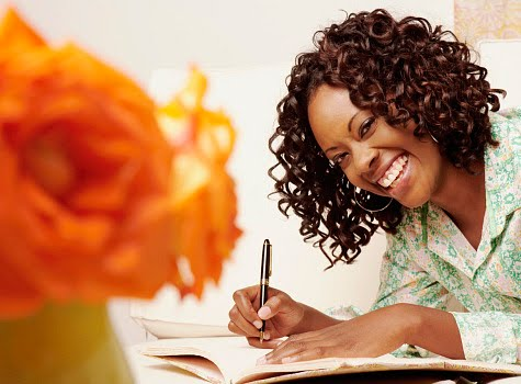 Black Woman Smiling and Writing